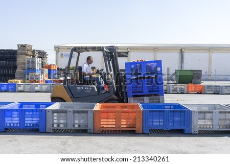 "NAOUSSA GREECE- AUGUST 20 2014: A worker transporting boxes with fruits of Agricultural Cooperative of Naoussa Greece. The famous ""Naoussa Peaches"" are the area's main product. Fruit production. - stock photo"