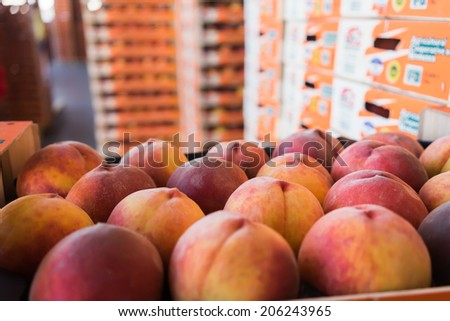 "NAOUSSA, GREECE- JULY 10, 2014: Products of Agricultural Cooperative of Naoussa, Greece, stacked in boxes. The famous ""Naoussa Peaches"", are the area's main product. Fruit production. - stock photo"