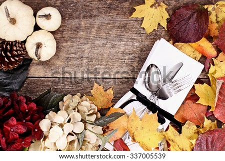 Napkin and cutlery over a rustic background with copy space. - stock photo
