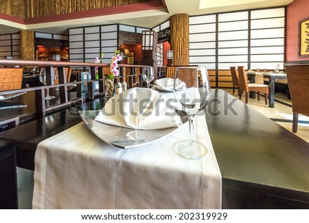 Napkin on the table of oriental  style interior of the asian, japanese restaurant. Interior design. - stock photo