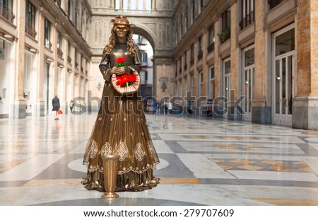 NAPLES, ITALY - 08 OCTOBER, 2012: Street actor dressed as a golden lady statue with roses. Trade center, Naples. - stock photo