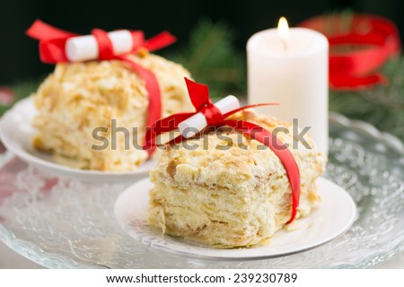 Napoleon cake decorated with red ribbon and small paper with Christmas wishes on white round plate. White candle, christmas tree branch on background - stock photo