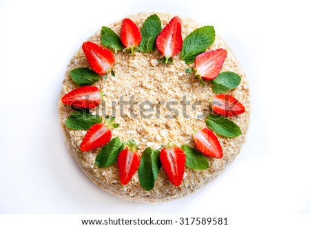 Napoleon cake filled with pastry cream on a white background decorated with fruits and flowers. Natural light, selective focus. - stock photo