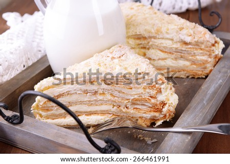 Napoleon cake on wooden tray on table close-up - stock photo