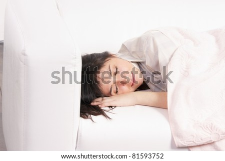 Napping young brunette woman tuck with plaid