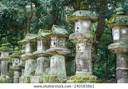 NARA, JAPAN - APRIL 12: Stone lanterns at Kasuga-taisha shrine on April 12, 2014 in Nara. The shrine is famous for its many bronze lanterns, as well as the many stone lanterns.