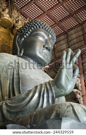 NARA, JAPAN - APRIL 10: The Great Buddha in Todai-ji temple on April 10, 2014 in Nara. It is a Buddhist temple complex which houses the world's largest bronze statue of the Buddha Vairocana (Daibutsu) - stock photo