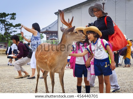 NARA,JAPAN- MAY 25, 2016: Kids and tourists playing wild deer in Nara on May 25, 2016. The deer in Nara have been regarded as heavenly animals, protecting the city and the country - stock photo