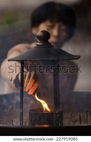 NARA,JAPAN, NOVEMBER 18, 2011 : A Japanese woman is igniting an incense stick before praying at the Todai-ji temple in Nara near Kyoto. - stock photo