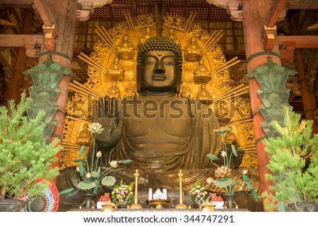 NARA, JAPAN - NOVEMBER 19, 2015: The Todaiji Buddha. It is considered  the world's largest bronze statue of the Buddha Vairocana. - stock photo