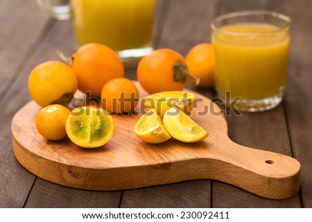 Naranjilla or Lulo fruits (lat. Solanum quitoense) on wooden board with freshly prepared naranjilla juice in the back (Selective Focus, Focus on the naranjilla pieces in the front)  - stock photo