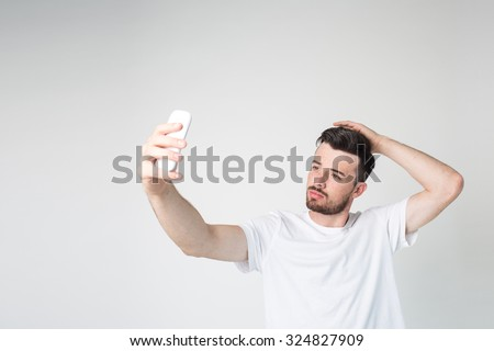 Narcissistic black-haired bearded man makes salfe. Isolated on light background