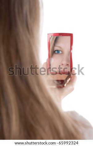 Narcissistic young woman looking at her face in the mirror - narcissism concept - stock photo