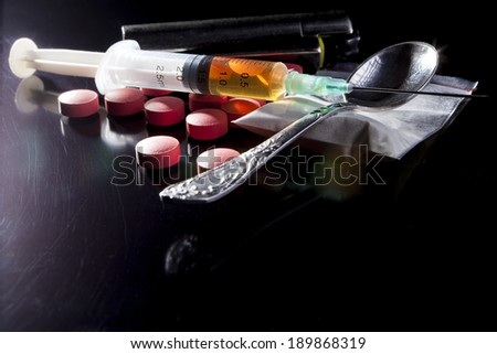Narcotics on black table with some reflection - stock photo