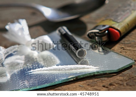 Narcotics on mirror with spoon and lighter in background. - stock photo