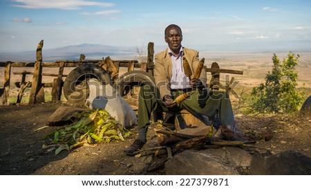 NAROK COUNTY, KENYA - OCTOBER 16, 2014 : African man in a suit sells corn  at the Kamandura Mai-Mahiu Narok Road near the Great Rift Valley in Kenya, Africa. - stock photo