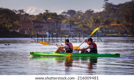NARRABEEN,AUSTRALIA - AUGUST 31, 2014: Two men paddle a canoe across Narrabeen Lakes on a fishing trip. The lake is also popular with paddle boarders and water skiers, and has BBQ facilities..