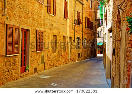 Narrow Alley with Old Buildings in Italian City of Volterra - stock photo
