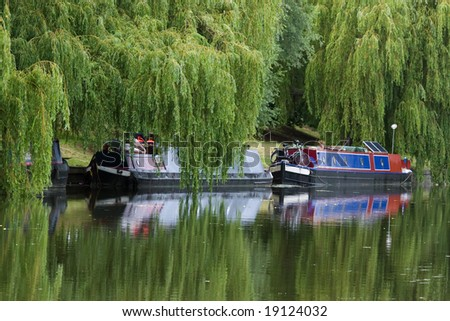 Narrow boat barge under the green trees (Cambridge, UK) - stock photo