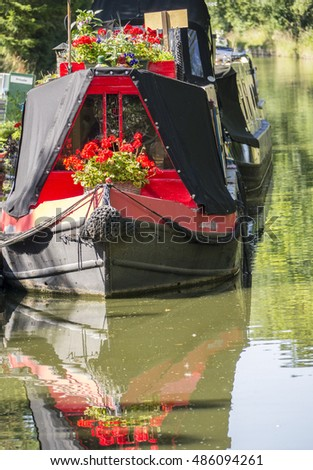 Narrow boat with flowers and reflection
