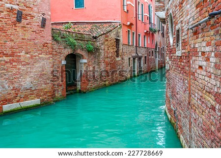 Narrow canal among old brick houses in Venice, Italy. - stock photo