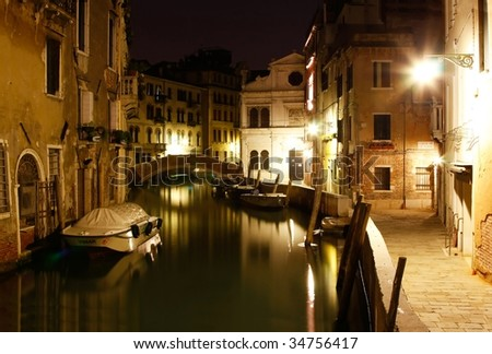 Narrow canal with beautiful church in Venice at midnight. (Italy) - stock photo