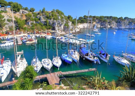 Narrow channel called calanque and sail boats tied to the wooden pier, Cassis, France - stock photo
