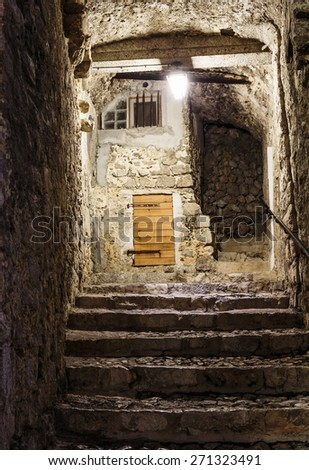 Narrow cobbled street in old town at night, France. - stock photo