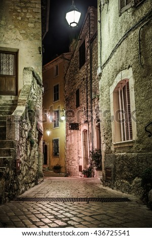 Narrow cobbled street with flowers in the old village Tourrettes-sur-Loup at night, France. - stock photo