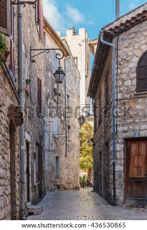 Narrow cobbled street with flowers in the old village Vence , France. - stock photo