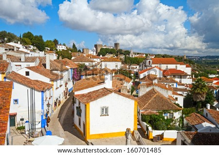 Narrow cobbled streets and traditionally painted houses in Obidos, Portugal. - stock photo