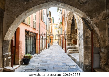 Narrow cobblestone street with colorful buildings viewed though stone arch in medieval town Villefranche-sur-Mer on French Riviera, France. - stock photo