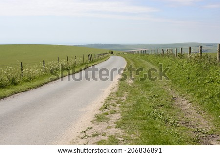 Narrow country lane on South Downs near Shoreham. West Sussex. England. Looking south over coast. - stock photo
