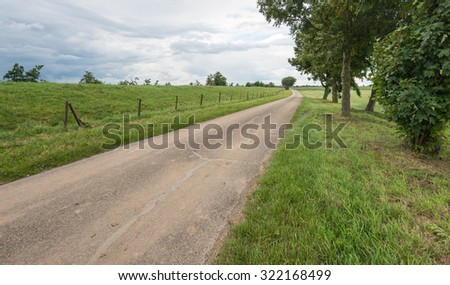 Narrow country road curves along a Dutch dike. There are dark clouds in the sky. The rain is coming. - stock photo