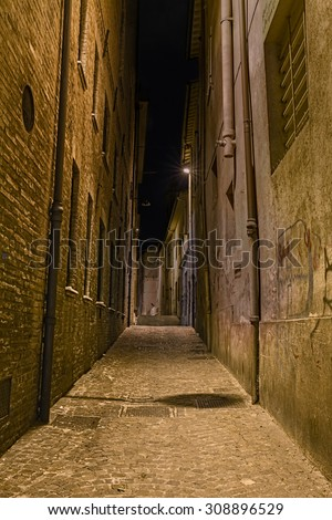 narrow dark alley in the old town - distressed alleyway in the italian city - grunge aged street at night 