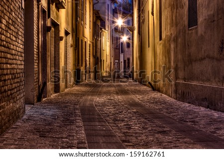 narrow dark alley in the old town - street at night in the Italian city - stock photo