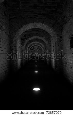 Narrow dark long corridor with illumination from below - stock photo
