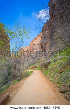 Narrow dirt walking trail leads into the main canyon in Zion National Park in southern Utah. - stock photo