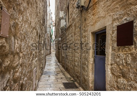 Narrow, empty and wet alley or pedestrian street at the Old Town in Split, Croatia.