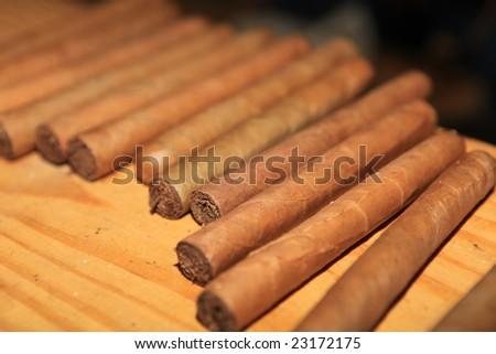 Narrow focus on collection of handmade cigars - stock photo