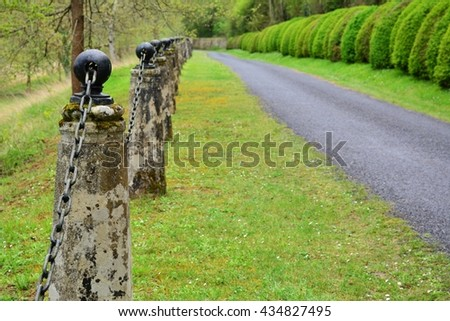 narrow focus on first old stone post iron ball with chain running into picture in a chain link fence - stock photo