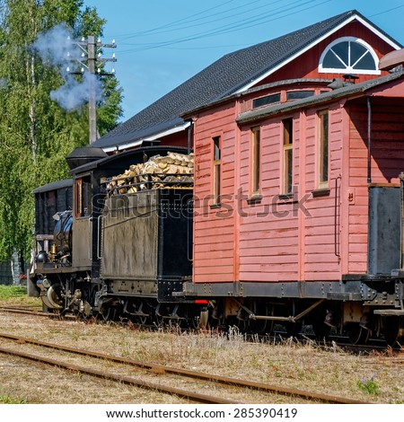 Narrow gauge steam locomotive with passenger carriage on rural station - stock photo