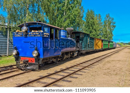 Narrow-gauge steam train pulling carriages. Minkio, Finland - stock photo