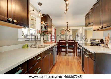 Narrow kitchen interior with deep brown cabinets and granite counter tops. Northwest, USA