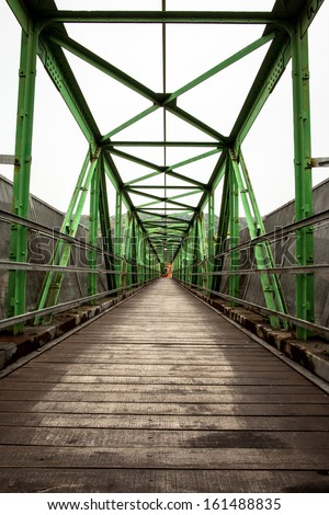 Narrow long footbridge with symmetrical metal structure