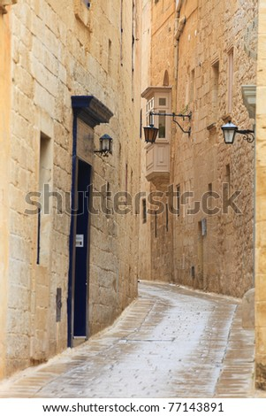 Narrow medieval stone paved street in Mdina the former capital of Malta - stock photo