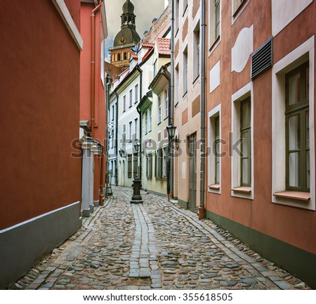 Narrow medieval street in the old Riga city. Riga is the capital and largest city of Latvia, a major cultural and historical center of the Baltic region with unique medieval architecture - stock photo