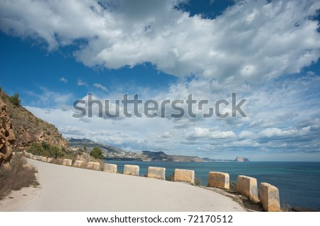 Narrow mountain road winding high above the sea - stock photo