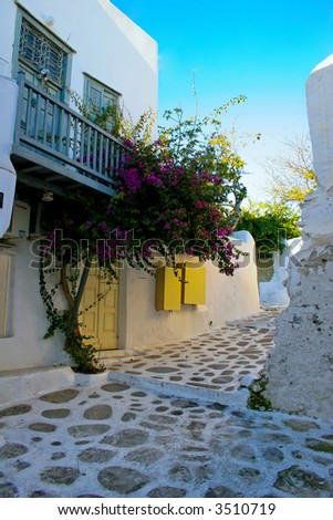 Narrow pathway of Mykonos detailing the white walls and blue trim