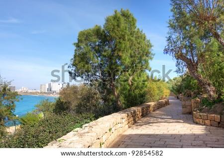 Narrow paved promenade in Yafo (Jaffa) with view on modern buildings of Tel Aviv along Mediterranean sea coastline in Israel. - stock photo